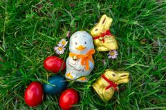 Lindt swiss golden milk chocolate bunny with red collar bell and a chocolate duck hidden in the grass Traditional chocolate on royalty free stock photo