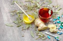 Lindte på trätabellen en kopp av lindte, honung, ingefära, termometer och minnestavlor traditionella boter för förkylningar och i arkivbild