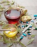 Lindte på trätabellen en kopp av lindte, honung, ingefära, termometer och minnestavlor traditionella boter för förkylningar och i royaltyfri fotografi