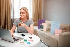 On-line ψωνίζοντας στο σπίτι Ο νέος ξανθός αγοραστής με το τσάι είναι ευχαριστημένος από τις μεγάλες εκπτώσεις της μαύρης Παρασκε στοκ εικόνα με δικαίωμα ελεύθερης χρήσης