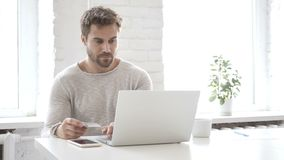 On-line ψωνίζοντας με την τραπεζική κάρτα από το όμορφο άτομο στο lap-top απόθεμα βίντεο