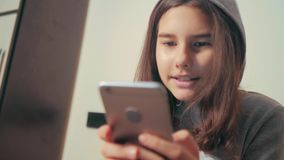 On-line ψωνίζοντας σε απευθείας σύνδεση λιανική υπηρεσία που εδρεύει Λίγο κορίτσι εφήβων στην κουκούλα γράφει ένα μήνυμα κουβεντι απόθεμα βίντεο