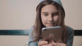On-line ψωνίζοντας σε απευθείας σύνδεση λιανική υπηρεσία που εδρεύει Λίγο κορίτσι εφήβων στην κουκούλα γράφει ένα μήνυμα κουβεντι φιλμ μικρού μήκους