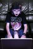 On-line. Boy shocked and tempt by the web-site content royalty free stock photo