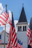 Line of American flags stand outside white church on Memorial Day. US flags outside church steeple blowing in wind on clear sunny day in May Royalty Free Stock Photos