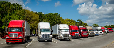 A Line of American Trucks. A line of large American trucks at a truck rest area. These are used for transporting heavy goods interstate, across America royalty free stock photography