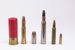 Line of ammunition isolated on white. Bullets and shotgun shells lined up and isolated on white Royalty Free Stock Image