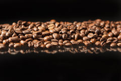 Line of Aromatic Roasted Coffee Beans Placed over Black Backgrou Stock Image