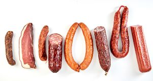 Line of assorted spicy seasoned sausages. And a portion of cured ham, bacon or kassler isolated on a panorama banner format white background Stock Image