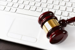 On-line auction. Gavel on white laptop, selective focus on metal part Stock Photography