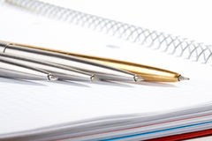 Line of ball-point pens lays. On a writing-book Stock Image