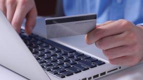 On-line-Banküberweisungen machend, hält die Hand des Mannes eine Kreditkarte beim Eingeben von Daten in Laptop Abschluss oben stock footage