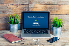 On line banking on computer. Transaction completed text in the s. Wooden desk with laptop, mobile phone and plants Royalty Free Stock Photos