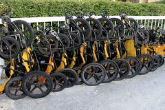 Line of beach tricycles secured to fence Royalty Free Stock Images