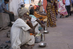 Line of Beggars Sitting Outside a Temple in India. Mathura, Agra, India – October 13, 2016: Line of beggars seeking alms from worshipers outside a temple in Stock Photo