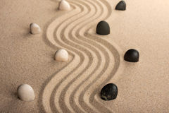 Line black and white  stones, standing on the sand Stock Images