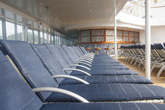 LIne of Blue Chaise Lounges on Deck of Ship. A line of blue chaise lounges on a ships deck stock photo
