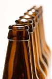 Line of bottles isolated on white. Empty bottle necks, shallow depth of field Royalty Free Stock Photo
