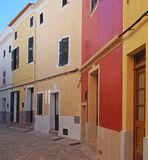 Line of brightly painted traditional houses on a cobbled quiet curved empty street in ciutadella menorca with wooden shutters an stock photos
