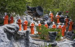 A line of Buddhist monk statues approaching the The Golden Temple at Dambulla, Sri Lanka. A line of Buddhist monk statues pray as they approach the The Golden Royalty Free Stock Image