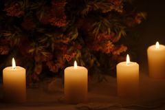 Line of burning candles with dried flowers. Four burning candles in darkness with a bouquet of dried flowers in the background on a festive embroidered Royalty Free Stock Photos