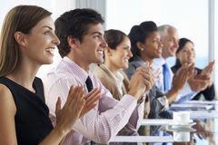 Line Of Business People Listening To Presentation Seated At Glas Stock Photo