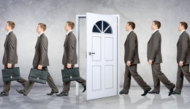 Line of businessmen going through door Stock Photography