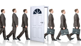 Line of businessmen going through door Royalty Free Stock Image