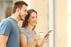 On line buyers shopping on a mall. On line buyers shopping with a smart phone and credit card on a mall stock photos