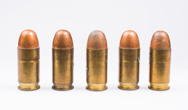 Line of 38 caliber bullets. Brass shells that are old and scuffed isolated on white Royalty Free Stock Photos