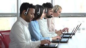 Line of call centre employees working on a laptop computers. Business people group with headphones giving support to customers in bright office stock video footage