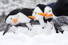 Line of carol singing snowmen Stock Photos