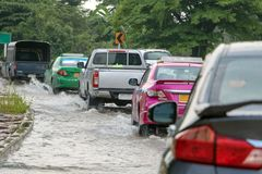A line of cars ride on a road under water stock images