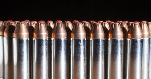 Line of cartridges with red tipped bullets Royalty Free Stock Photos