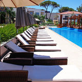 Line of chaise longues by the pool. Line of sun beds for tan by the pool , square toned image stock image