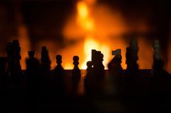 Chess pieces silhouette backlit by fireplace stock photo