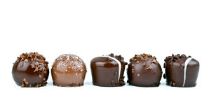Line of chocolate truffles on white background. Row of chocolate truffles on white background royalty free stock photo