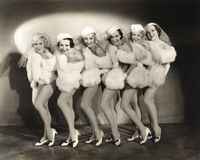 Line of chorus girls in white fur stock images