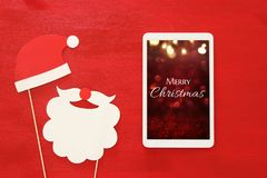 On line christmas holiday shopping concept. Santa claus red and beard hat next to tablet device.  Stock Photos