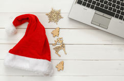 On line christmas holiday shopping concept. Santa claus red hat next to computer keyboard Royalty Free Stock Photos