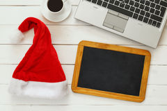 On line christmas holiday shopping concept. Santa claus red hat next to computer keyboard, blank blackboard and cup of coffee Royalty Free Stock Photo