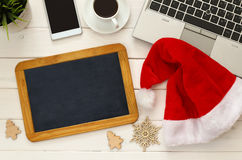 On line christmas holiday shopping concept. Santa claus red hat next to computer keyboard, blank blackboard and cup of coffee Stock Photography