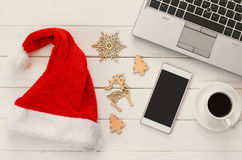 On line christmas holiday shopping concept. Santa claus red hat next to computer keyboard and cup of coffee Royalty Free Stock Photos