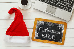 On line christmas holiday shopping concept. Santa claus red hat next to computer keyboard and cup of coffee Stock Photo