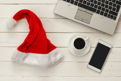On line christmas holiday shopping concept. Santa claus red hat next to computer keyboard and cup of coffee Royalty Free Stock Photo