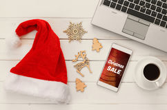 On line christmas holiday shopping concept. Santa claus red hat next to computer keyboard and cup of coffee Royalty Free Stock Photography