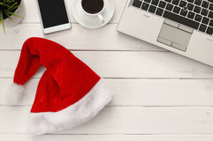 On line christmas holiday shopping concept. Santa claus red hat next to computer keyboard and cup of coffee Stock Image