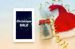 On line christmas holiday shopping concept. Santa claus red hat next to tablet device Royalty Free Stock Photo