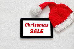 On line christmas holiday shopping concept. Santa claus red hat next to tablet device Stock Photography