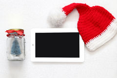 On line christmas holiday shopping concept. Santa claus red hat next to tablet device Stock Photo